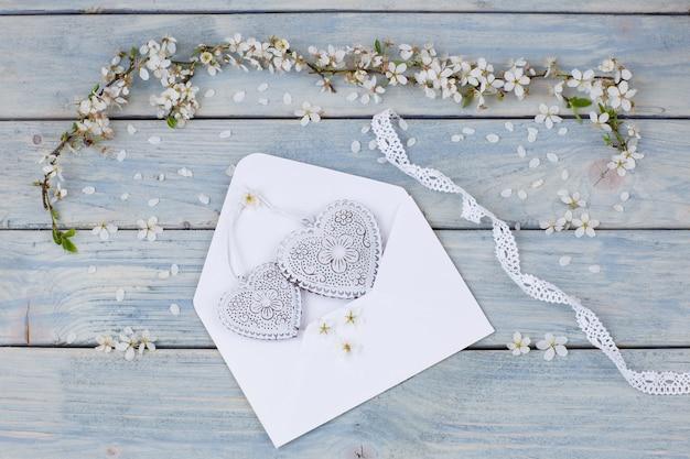 Branches de cerisier blanc en fleurs et une enveloppe avec des coeurs blancs