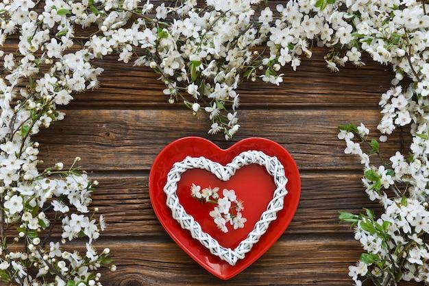 Branches de cerisier en fleurs blanches avec forme de coeur plat rouge.