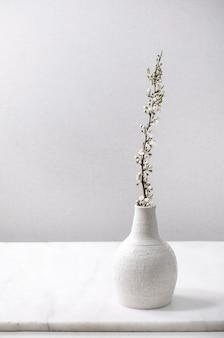 Branches de cerisier en fleurs dans un vase en porcelaine blanche artisanale sur une table en marbre blanc.