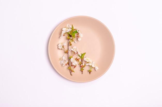 Branches de cerisier en fleurs sur la plaque sur blanc