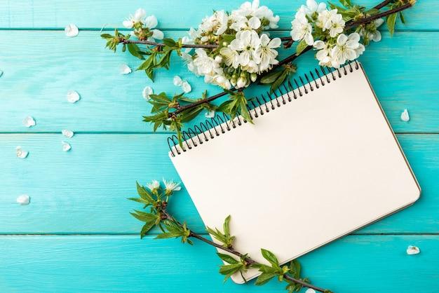 Branches de cerisier en fleurs de printemps et cahier sur fond en bois bleu.