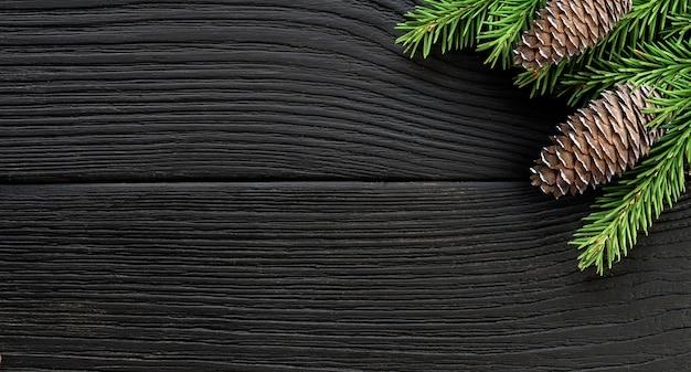 Branches et cônes de sapin de noël sur un fond rustique en bois noir. espace de copie