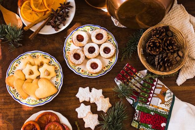 Branches de conifères et cônes près des biscuits et des épices
