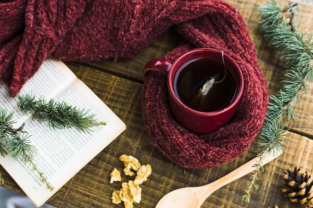 Branches de conifères et livre près de thé et pull