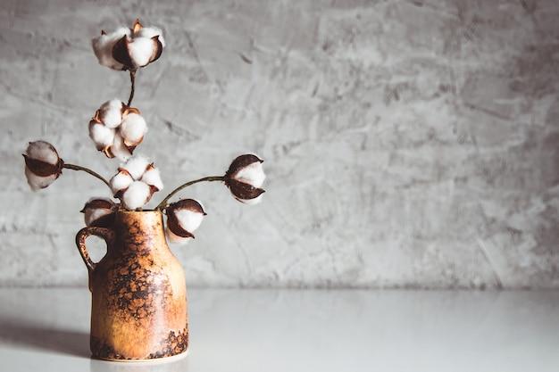 Branches de coton dans un vase en osier marron sur fond d'un mur gris-bleu