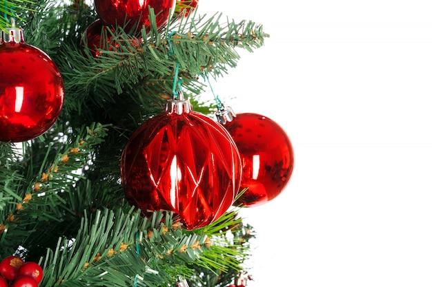 Branches d'épinette avec des boules rouges contre blanc