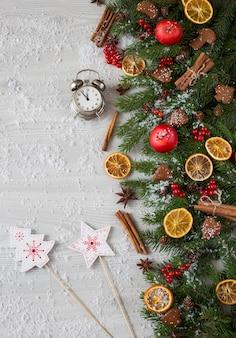 Branches d'épinette, décor, cannelle, tranches d'orange et un réveil, sur l'horloge 23.55