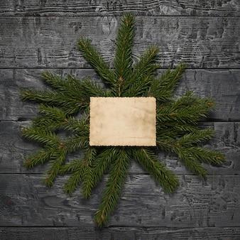 Branches d'épinette avec une feuille de vieux papier sur une table en bois.