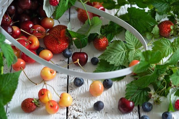 Branches et feuilles de baies et assortiment de fraises, framboises, myrtilles, cerises