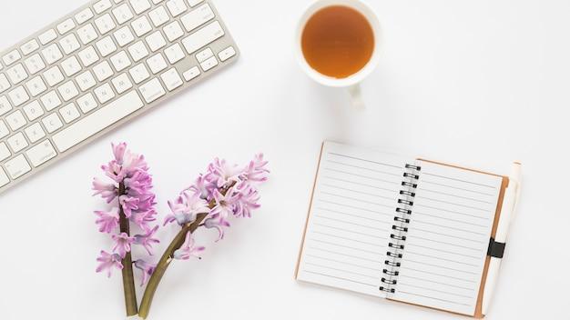 Branches de fleurs avec carnet, clavier et thé