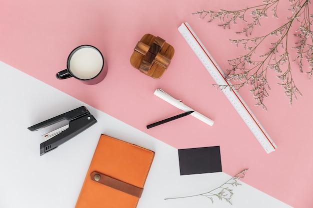 Branches de fleurs, règle échelle, une tasse de lait, stylo, crayon, agrafeuse, carnet de croquis et bloc en bois.