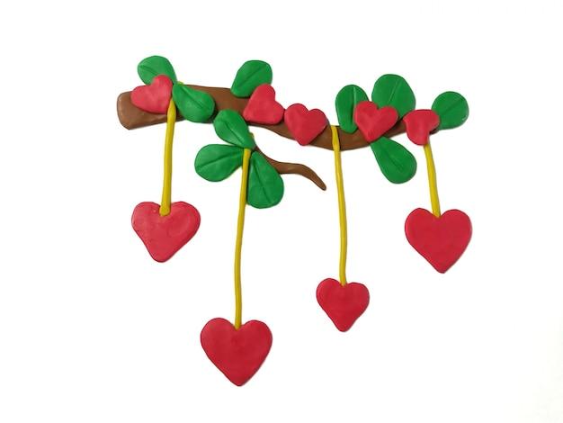 Les branches en forme de coeur rouge en pâte à modeler sur du blanc
