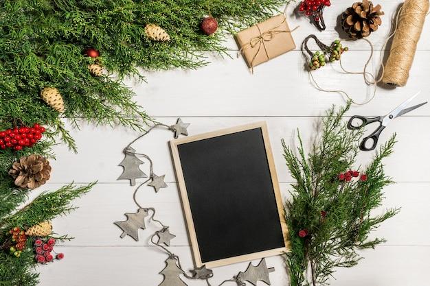 Branches de genévrier avec un décor de noël. noël, fond de nouvel an. branches de conifères de genévrier et tableau d'écriture noir. vue de dessus, design plat. arbre de noël sur fond en bois blanc.