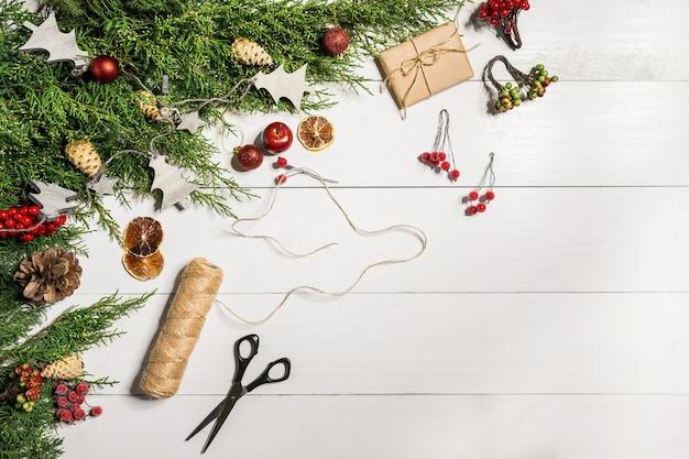 Branches de genévrier avec un décor de noël. noël, fond de nouvel an. branches de conifères de genévrier. vue de dessus, design plat. arbre de noël sur fond en bois blanc.