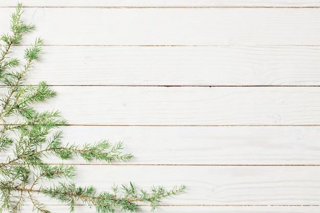 Branches de genévrier sur un fond en bois blanc. fond de noël et nouvel an