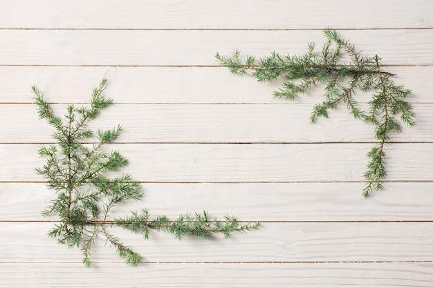 Branches de genévrier sur un fond en bois blanc. noël et nouveau