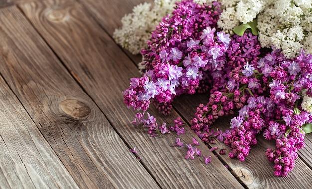 Branches de lilas frais en fleurs sur une table en bois sombre.