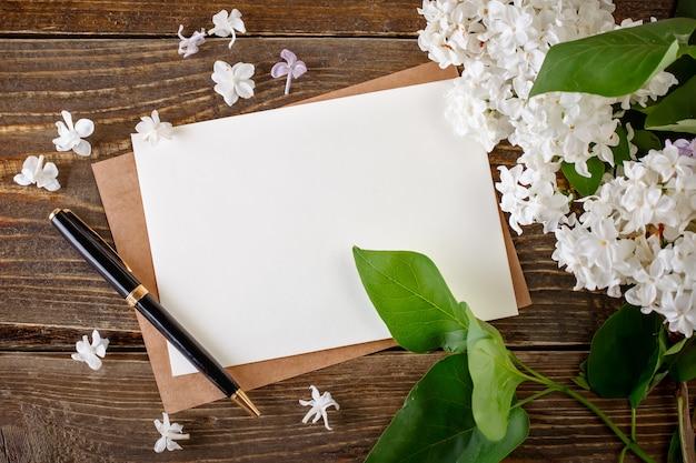 Branches de lilas se trouvant sur des planches en bois avec des cartes postales.