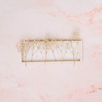 Branches de petites fleurs sur une planche en bois sur une table
