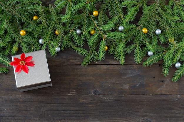 Branches de pin avec un décor et une boîte en argent pour un cadeau et une fleur rouge