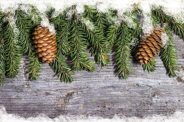 Branches de pin décorées avec des cônes sur l'espace libre de table en bois. décorations de noël