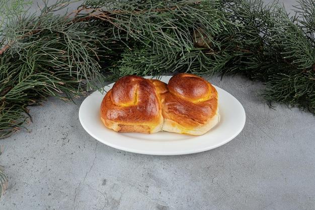 Branches de pin derrière un plateau de pain sucré sur table en marbre.