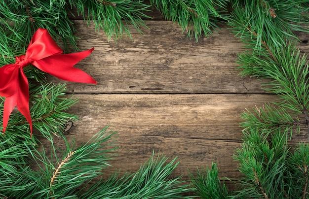 Branches de pin fraîches et noeud en satin rouge