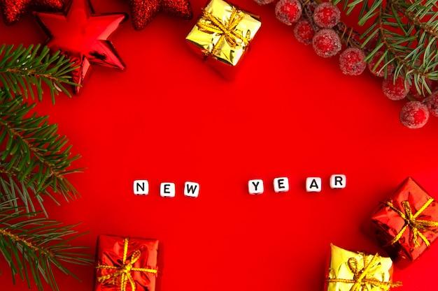 Branches de pin vert avec des jouets de noël rouges, des coffrets cadeaux, des baies glacées rouges et l'inscription du nouvel an sur des cubes sur fond rouge