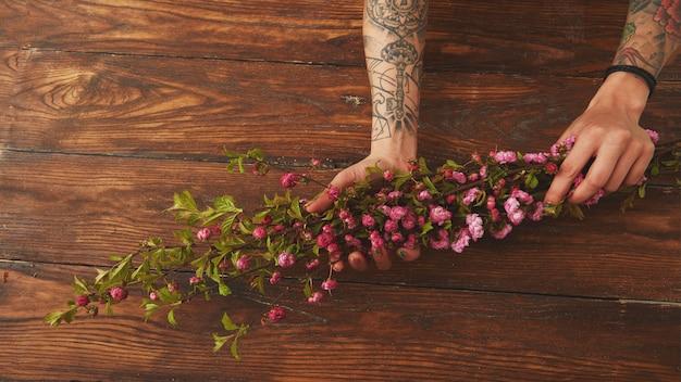 Branches de sakura dans les mains des femmes sur un vieux fond en bois