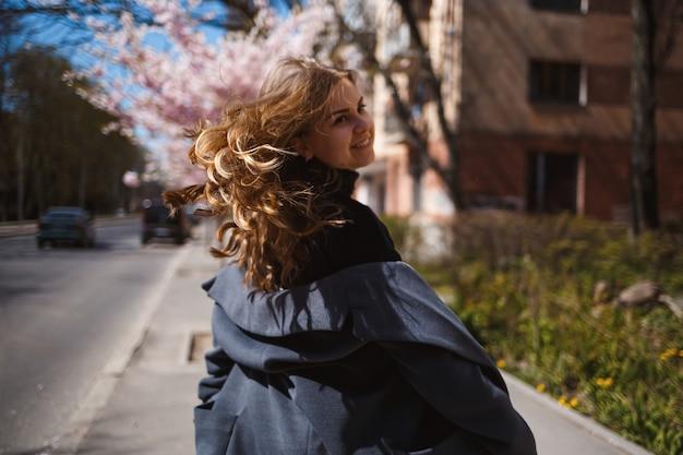 Branches de sakura avec des fleurs sur un arbre dans les rues de la ville. une femme élégante court dans la rue avec un sakura en fleurs. superbe fille à la mode à l'extérieur. fleurs d'arbre sakura.