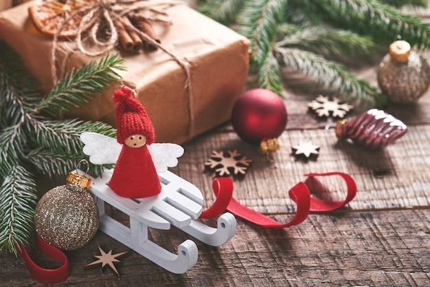 Branches de sapin ange de noël drôle et coffrets cadeaux sur fond neigeux d'hiver avec des branches enneigées. concept de noël ou d'hiver.