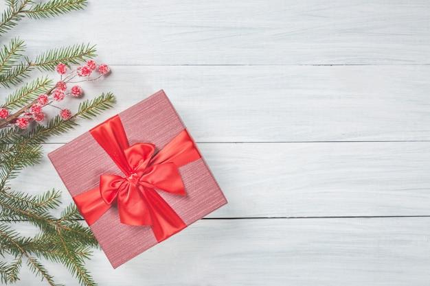 Branches de sapin, baies rouges congelées et coffret cadeau avec ruban rouge sur bois blanc