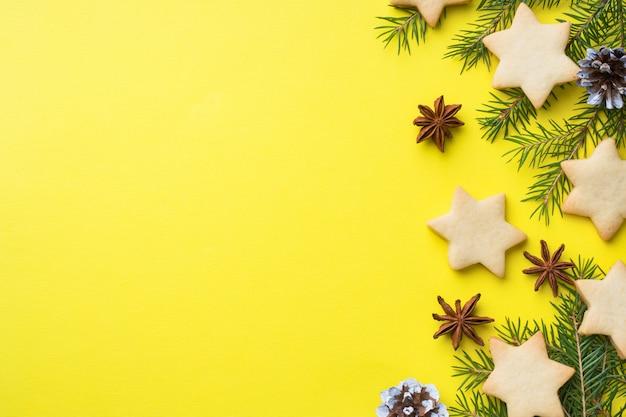 Branches de sapin, biscuits et guimauves sur jaune