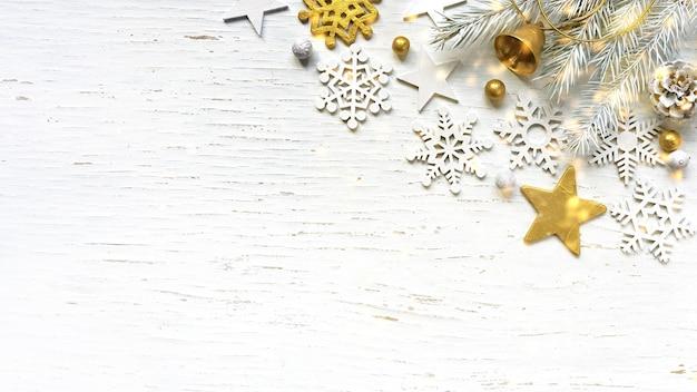 Branches de sapin blanc de noël cône de pin vieil or jingle bell et décorations blanches sur fond de bois blanc avec des lumières dorées incandescentes