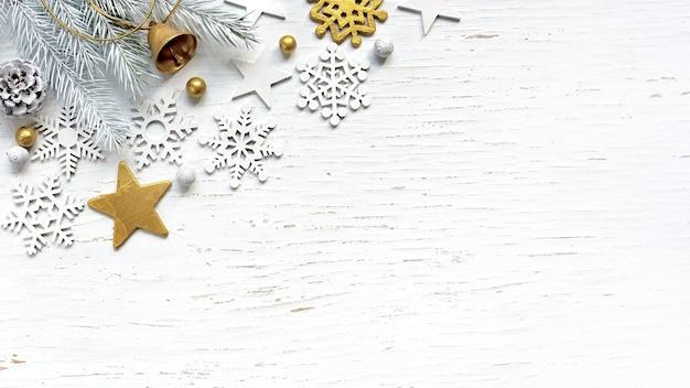 Branches de sapin blanc de noël cône de pin vieil or jingle bell et décorations blanches sur fond de bois blanc.