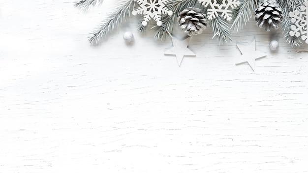 Branches de sapin blanc de noël pommes de pin et décorations sur fond de bois blanc. fond d'hiver avec espace de copie.
