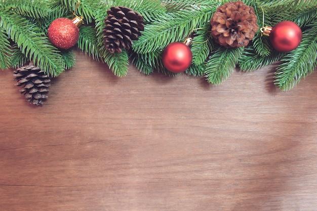 Branches de sapin, boule de noël rouge et pommes de pin avec décoration sur une planche de bois.