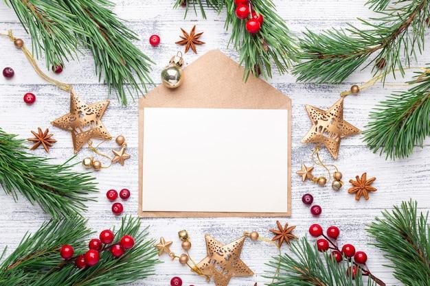 Branches de sapin, cadeaux et une enveloppe sur un fond en bois clair