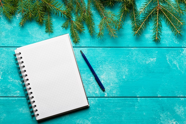 Branches de sapin et carnet avec un stylo sur fond de bois bleu.