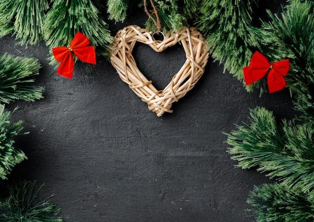 Branches de sapin avec coeur en bois sur fond noir