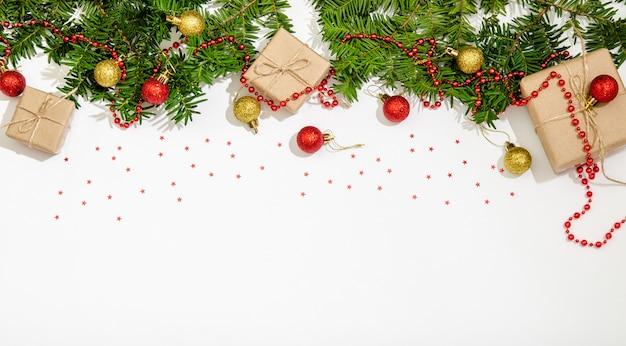 Branches de sapin, coffrets cadeaux, boules de noël de couleur rouge et or pour la décoration, perles rouges pour la décoration sur blanc