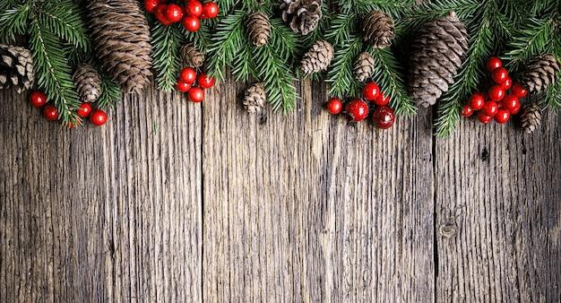 Branches de sapin, cônes et baies de noël rouges sur une vieille planche de bois. la composition de noël peut être utilisée pour l'arrière-plan du cadre de bordure. vue de dessus, espace de copie