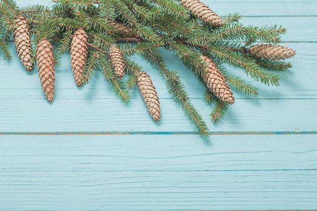 Branches de sapin avec cônes sur mur en bois bleu