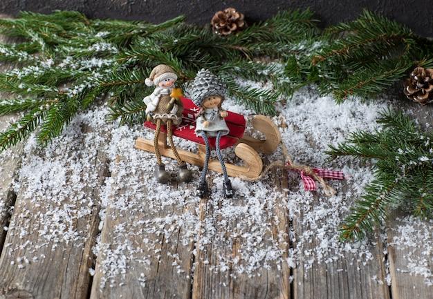 Branches de sapin, cônes, neige et deux personnages (un bonhomme de neige et une fille) assis sur une table en bois