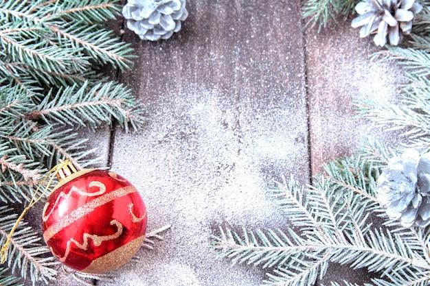 Branches de sapin couvertes de neige, pommes de pin et boule de noël rouge sur des planches de bois couvertes de neige.