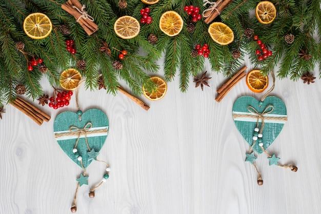 Branches de sapin, décor, baies, tranches d'orange, cannelle et deux coeurs en bois faits à la main