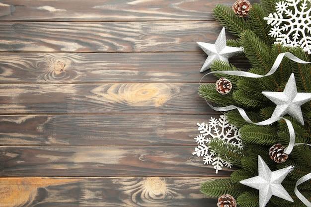 Branches de sapin avec décoration de noël en argent sur fond marron