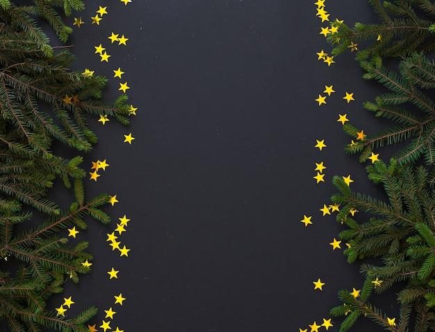 Branches de sapin et étoiles dorées sur surface noire