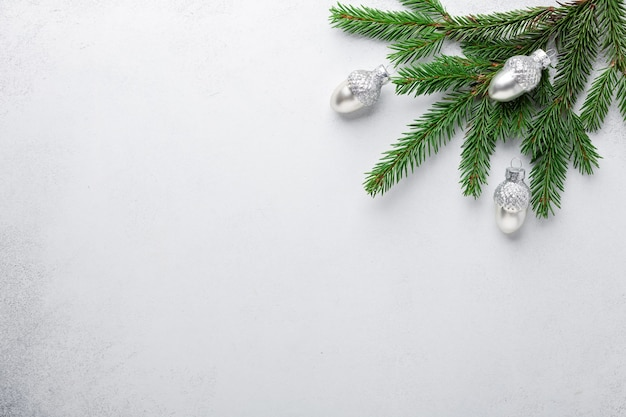 Branches de sapin avec des glands décoratifs en argent sur fond de pierre