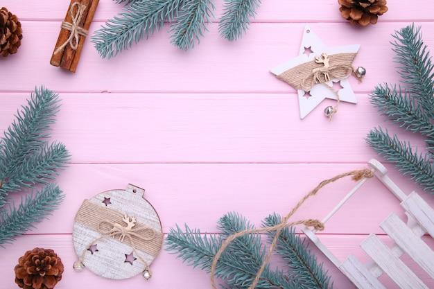 Branches de sapin avec des jouets de noël sur fond rose